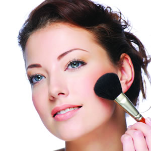 A girl doing makeup focusing on cheek color